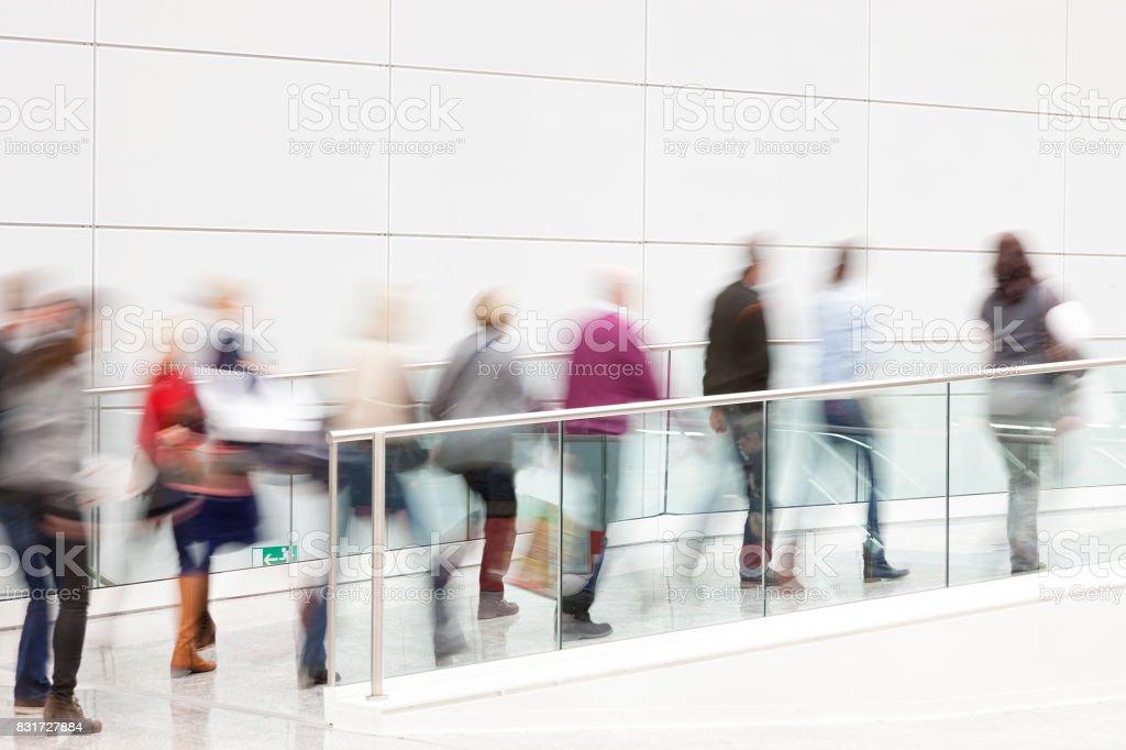 People Walking Through The White Hallway stock photo