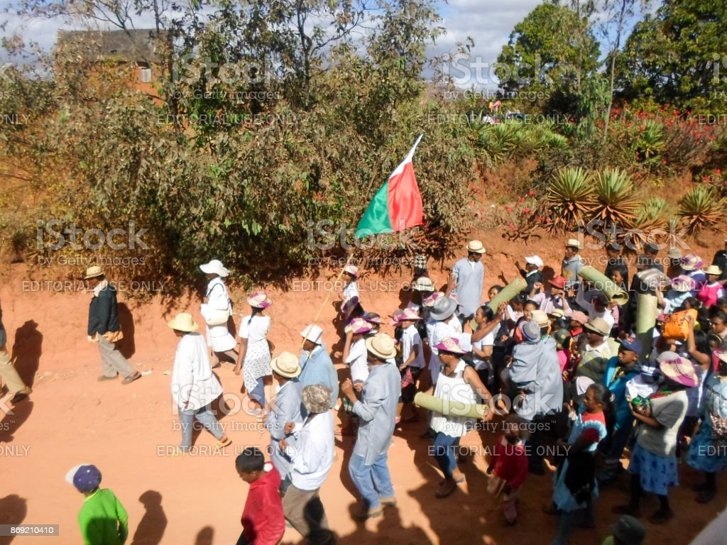 People walking to an ancestral tomb singing, dancing and carrying mats stock photo