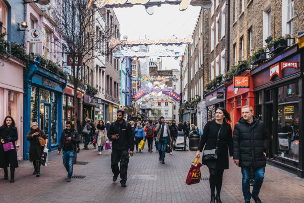 People walking under Bohemian Rhapsody themed Christmas lights in Carnaby Street, London, UK. London, UK - December 19, 2018: People walking under Bohemian Rhapsody themed Christmas lights in Carnaby Street, pedestrianised shopping street in Soho with over 100 shops and restaurants. carnaby street stock pictures, royalty-free photos & images