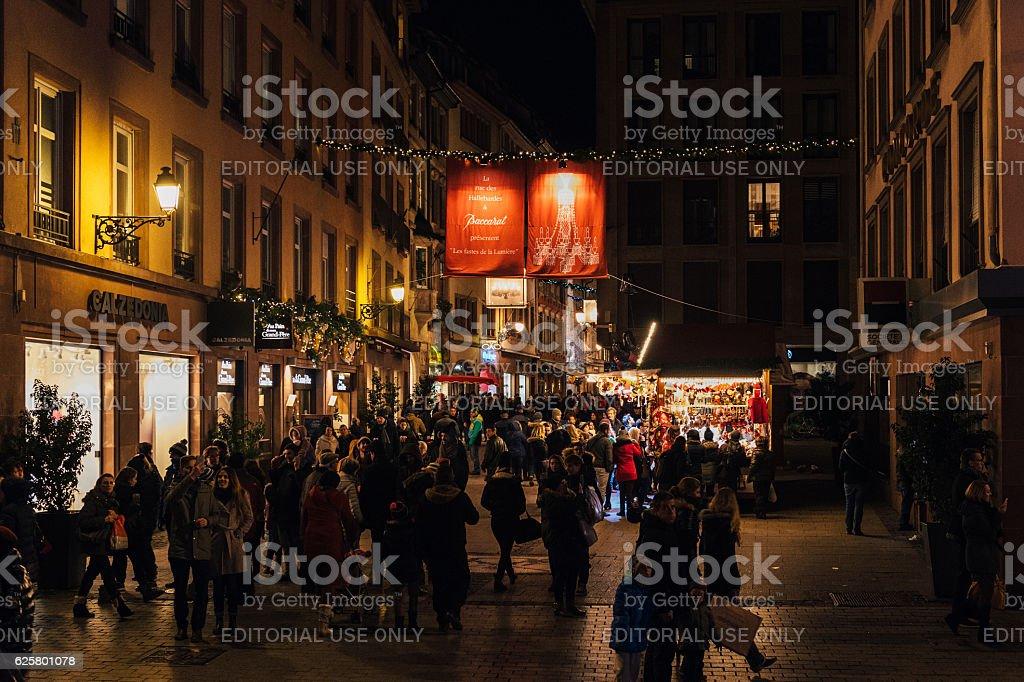 People walking under Crystal chandeliers rue des Hallebardes stock photo