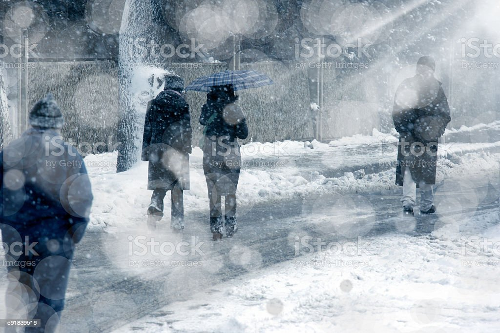 people walking under snow stock photo
