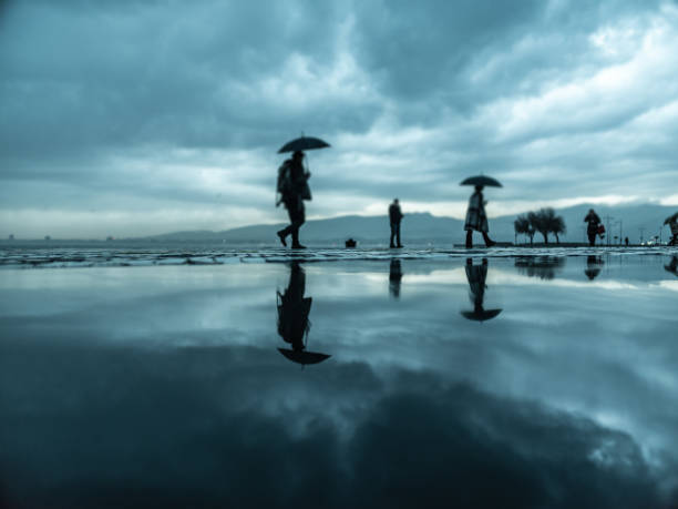 People walking under the rain in the rainy day stock photo