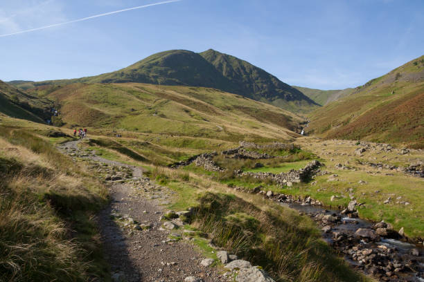 People walking up footpath to Helvellyn mountain near Glenridding stock photo