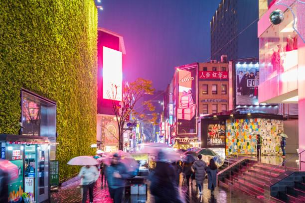 Gente caminando con paraguas en un día lluvioso en calle Myeong-dong en Seúl, Corea del sur por la noche, - foto de stock