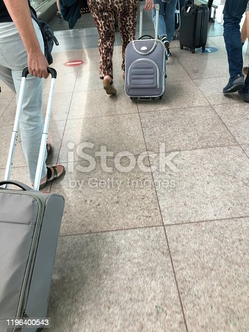 People walking with wheeled suitcase at Barcelona International airport, Spain