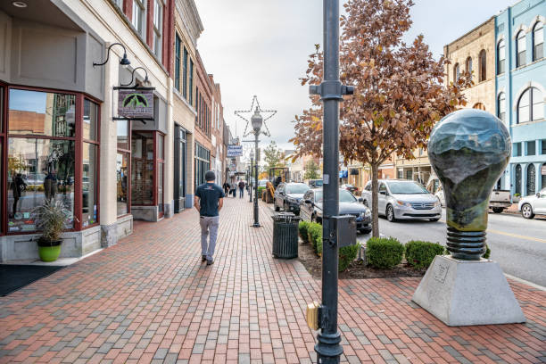 People wander Main Street area past Misty Morning sculpture stock photo