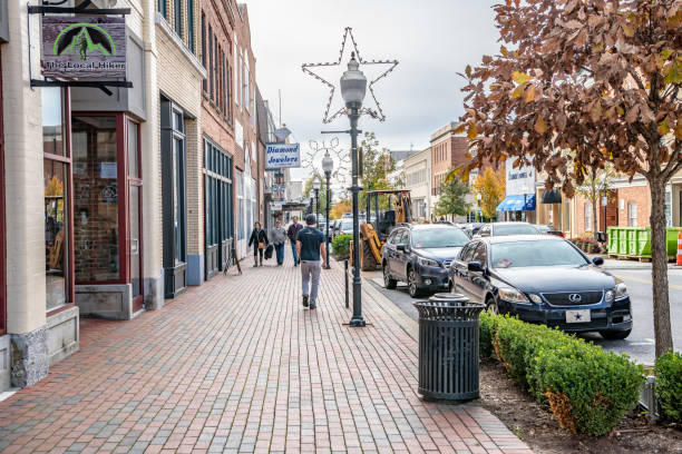 People wander the charming Main Street area downtown Spartanburg, S.C. / USA - November 16, 2019: People wander the charming Main Street area downtown. Spartanburg is very scenic. spartanburg stock pictures, royalty-free photos & images