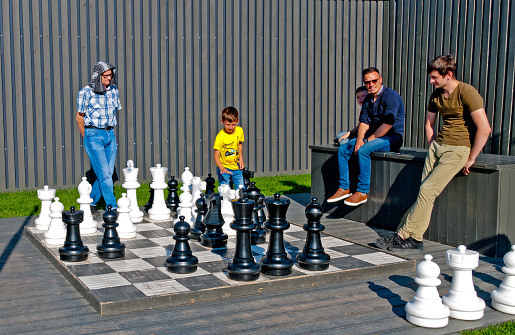People watch a boy playing chess on New Holland Island. St Petersburg