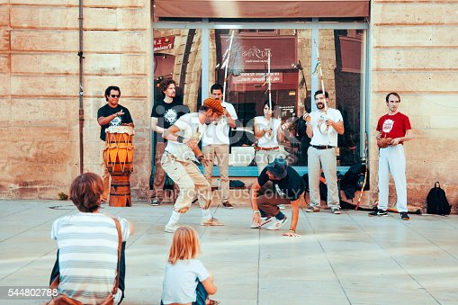 Bordeaux, France - August 24, 2015: People watch a homeless streetdancer doing breakdance and dance moves in the streets of Bordeaux to earn some money