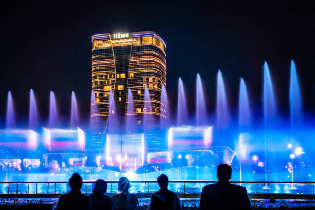 People watch dancing fountain in Tashkent City Park stock photo