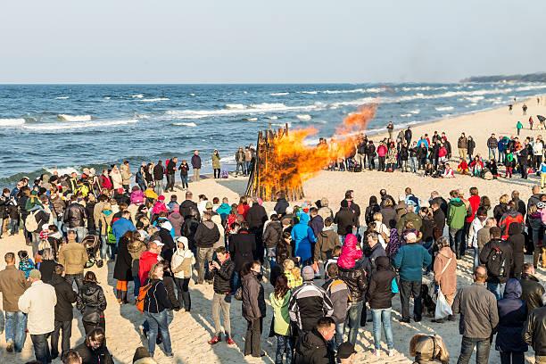 menschen beobachten sie die oster-am beach - osterfeuer stock-fotos und bilder