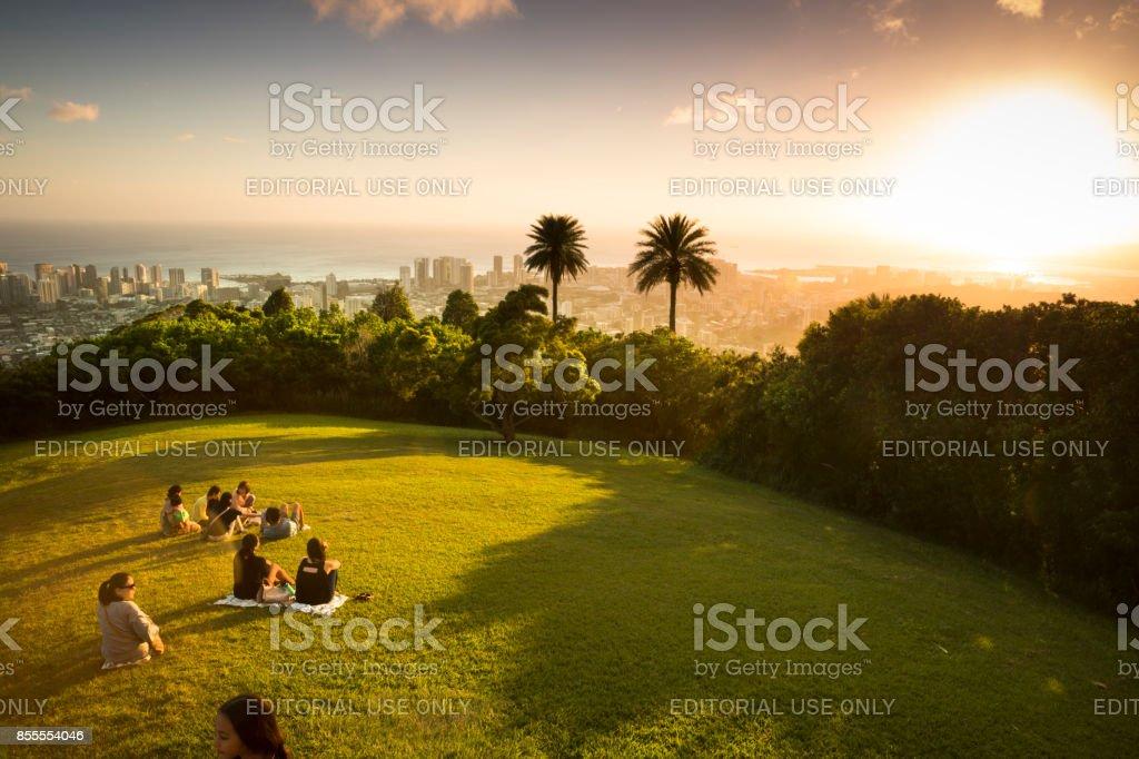 People watch the sunset over Honolulu Hawaii stock photo