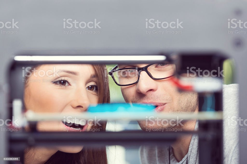 People watching 3D printout Two young people watching 3D printout. Focus on faces. 2015 Stock Photo