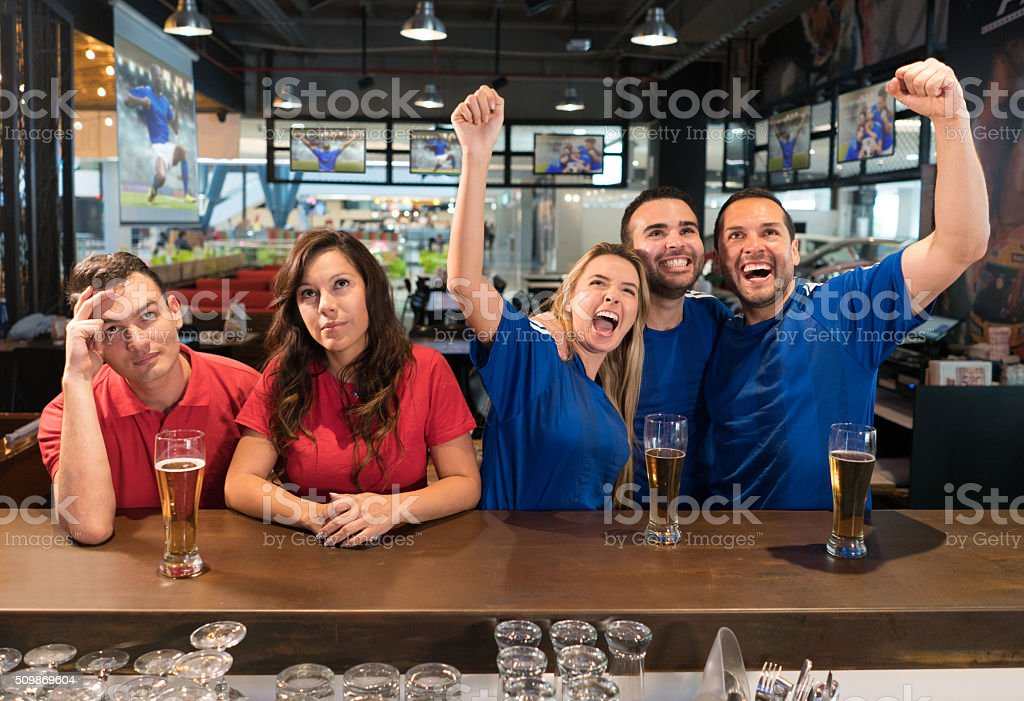 People watching a football game at a sports bar - foto de acervo