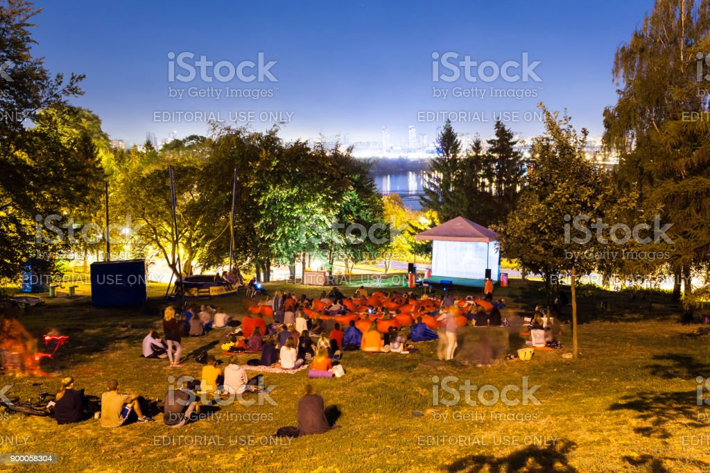 People watching a movie open air with night Kyiv cityscape, Ukraine....