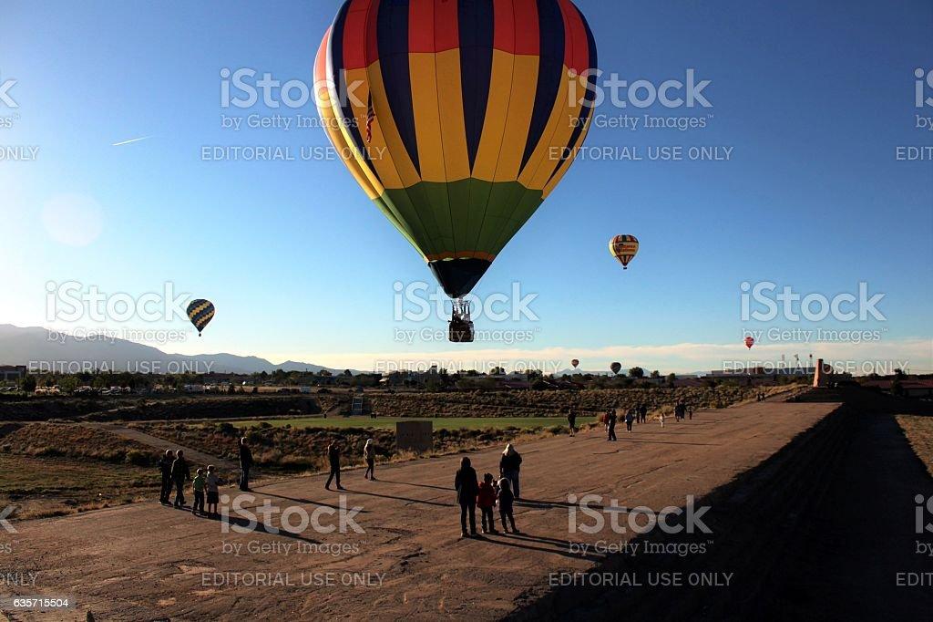 People watching as hot air balloons land royalty-free stock photo