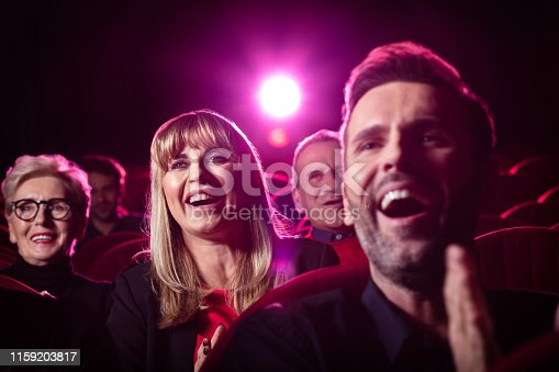 Shot of mature woman laughing while watching a movie in theater. Group of people watching a comedy film in cinema hall and laughing.