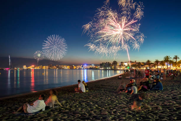 People watching fireworks at beach at dusk, Costa Brava, Catalunya, Spain stock photo