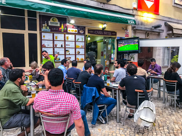 people watching football on big tv outside street cafe in lisbon. - serie televisiva foto e immagini stock