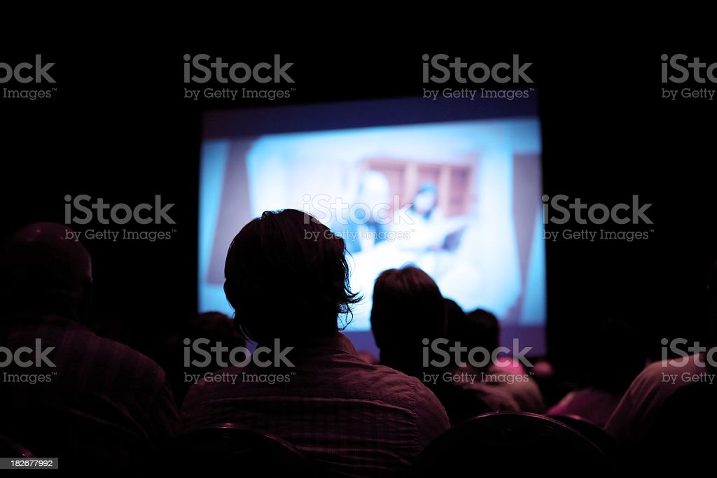 People watching movie in dark cinema stock photo
