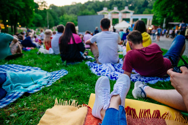 people watching movie in open air cinema in city park stock photo