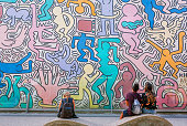 Pisa, Italy: People look at wall with artwork by modern artist Keith Haring, famous in pop-art style on 19 September 2018. American artist Keith Haring, popular street art figure, died in 1990.