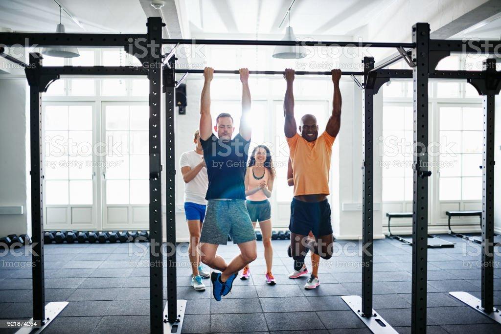 Menschen beobachten zwei Männer tun Chin ups in einem Fitnessstudio - Lizenzfrei Aktiver Lebensstil Stock-Foto