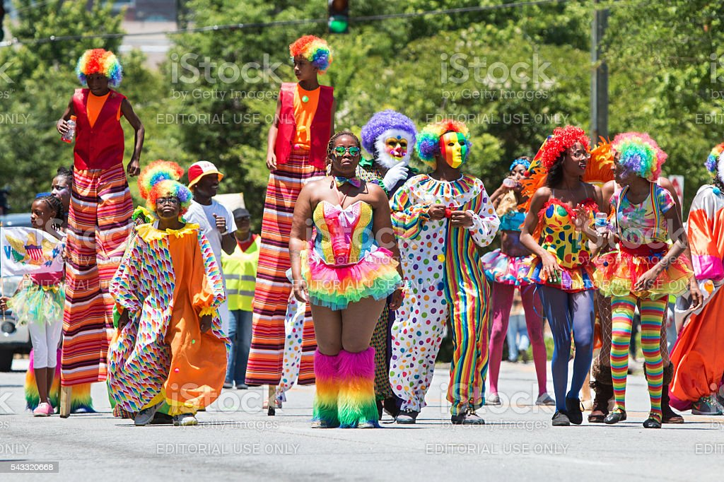 People wearing colorful clown costumes and walking on stilts...