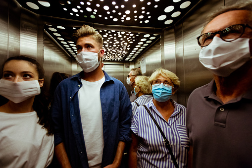 People wearing face mask in elevator