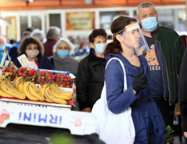 People wearing face masks and gloves for prevention of coronavirus stock photo