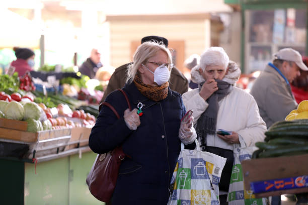 People, wearing face masks for protection, are shopping vegetables and fruits at marketplace stock photo