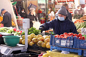 People, with face masks for protection, are shopping vegetables and fruits at marketplace in Sofia, Bulgaria - march 17, 2020.