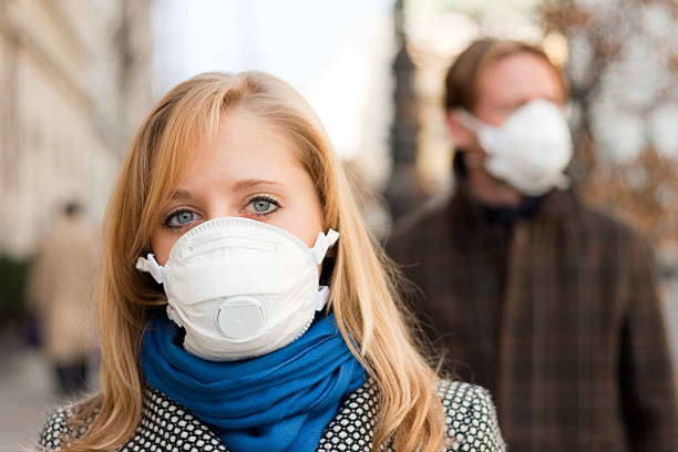 people wearing flu protection masks stock photo
