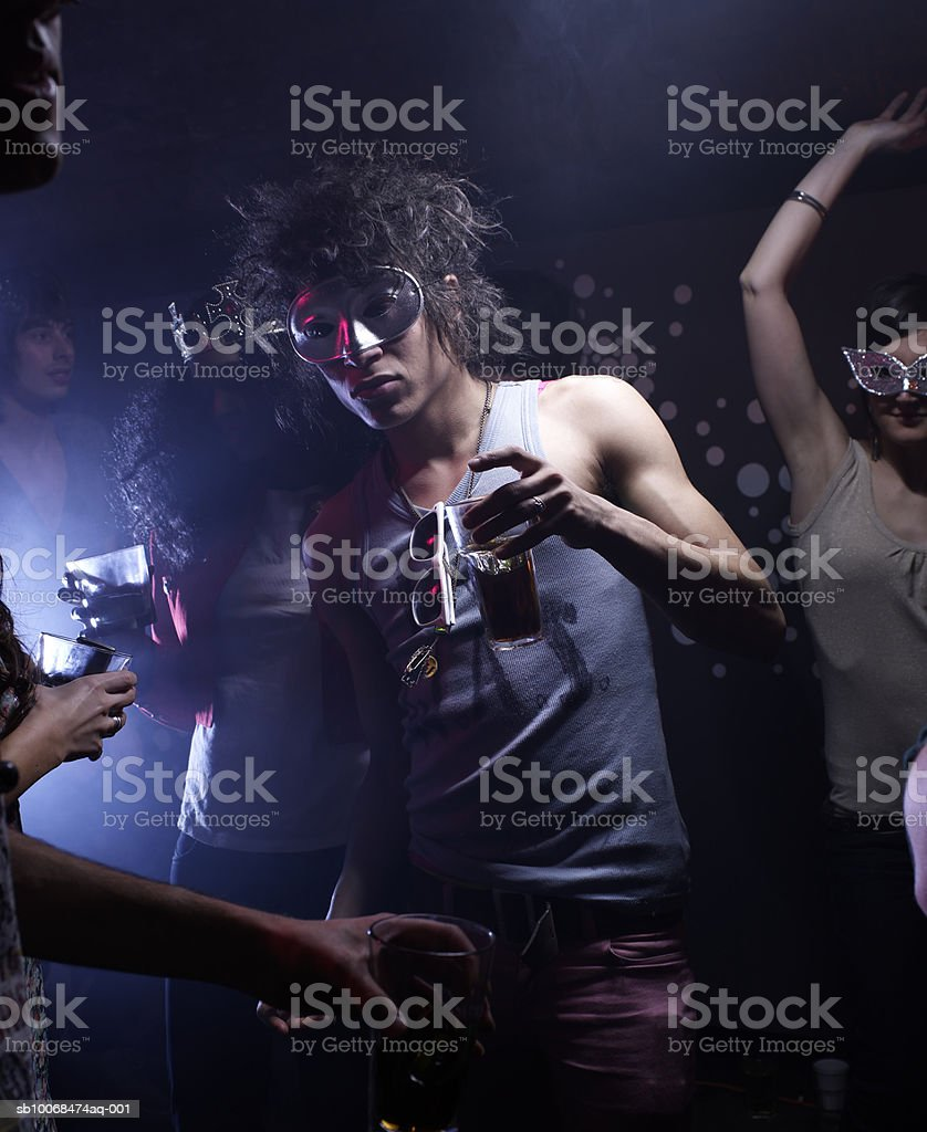 People wearing masks, dancing in night club royalty-free stock photo