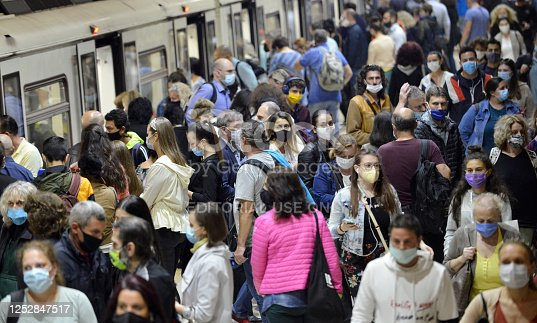 Sofia, Bulgaria - June 23 2020: Subway train passengers with protective masks crowding to get on and off subway station platform on Serdika Metro station.