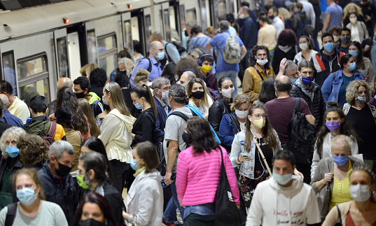 Sofia, Bulgaria - June 23 2020: Subway train passengers with protective masks crowding to get on and off subway station platform on Serdika Metro station.