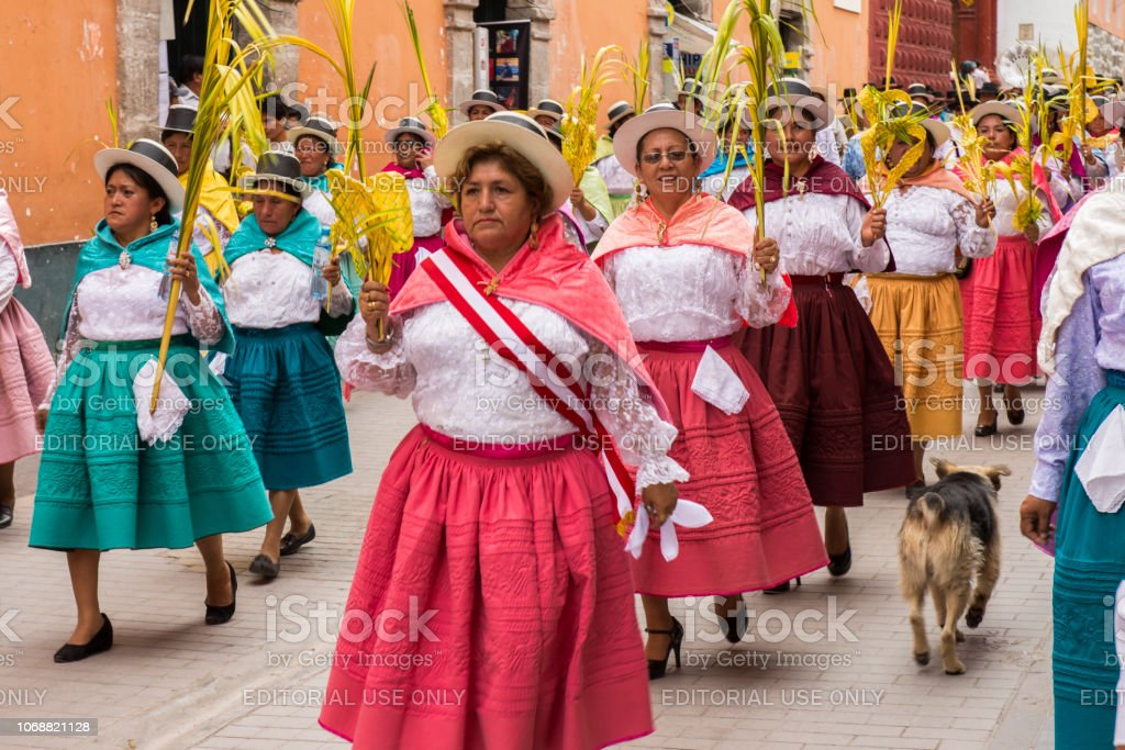 People wearing multicolored dresses and hats and a dog with them, marching during the celebration of the Palm Sunday of Easter at Ayacucho city, Peru. stock photo