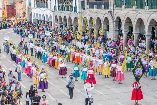 People wearing multicolored dresses and hats and a marching band during the celebration of the Palm Sunday of Easter at Ayacucho city, Peru. stock photo