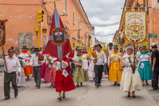 People wearing multicolored dresses and hats marching during the celebration of the Palm Sunday of Easter at Ayacucho city, Peru. stock photo