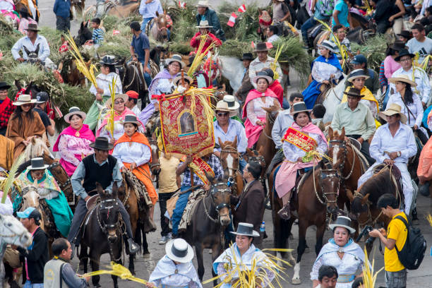 People wearing multicolored dresses and hats riding on horses during the celebration of the Palm Sunday of Easter stock photo