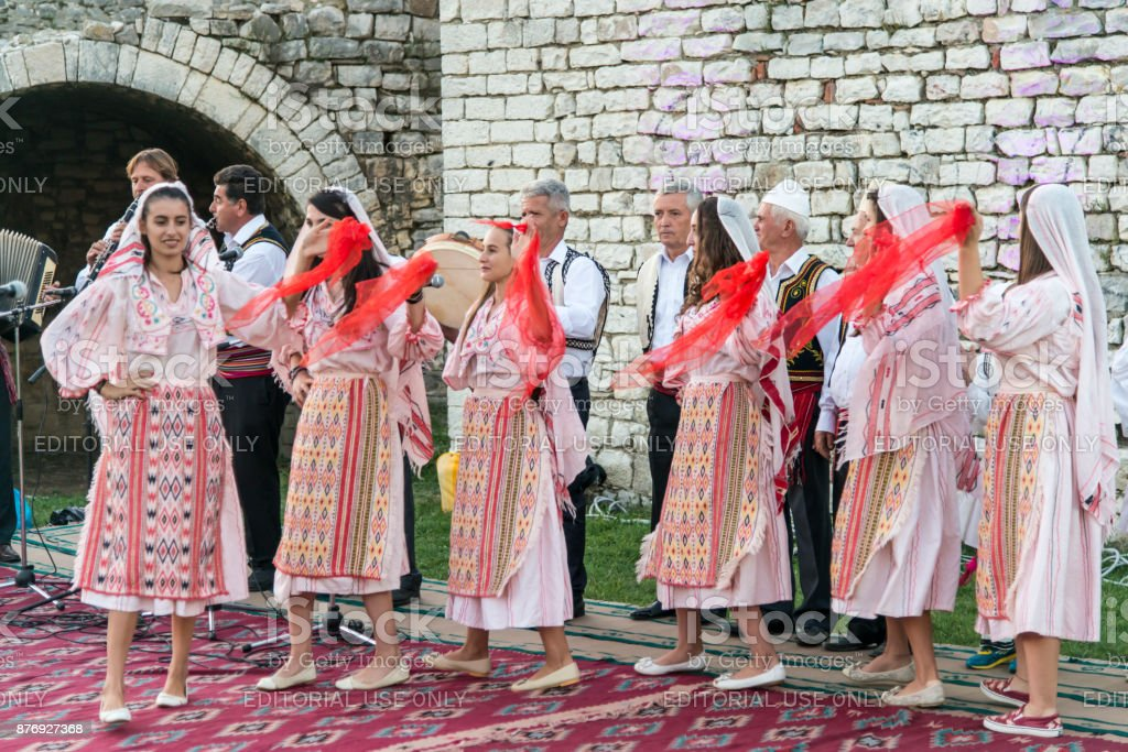 People wearing national costume dancing in traditional music festival in Berat castle in Albania stock photo