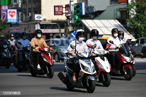 Taipei, Taiwan-05 04 2020:People riding motorcycles on a street of Taipei city and wearing protective masks during the global coronavirus epidemic.