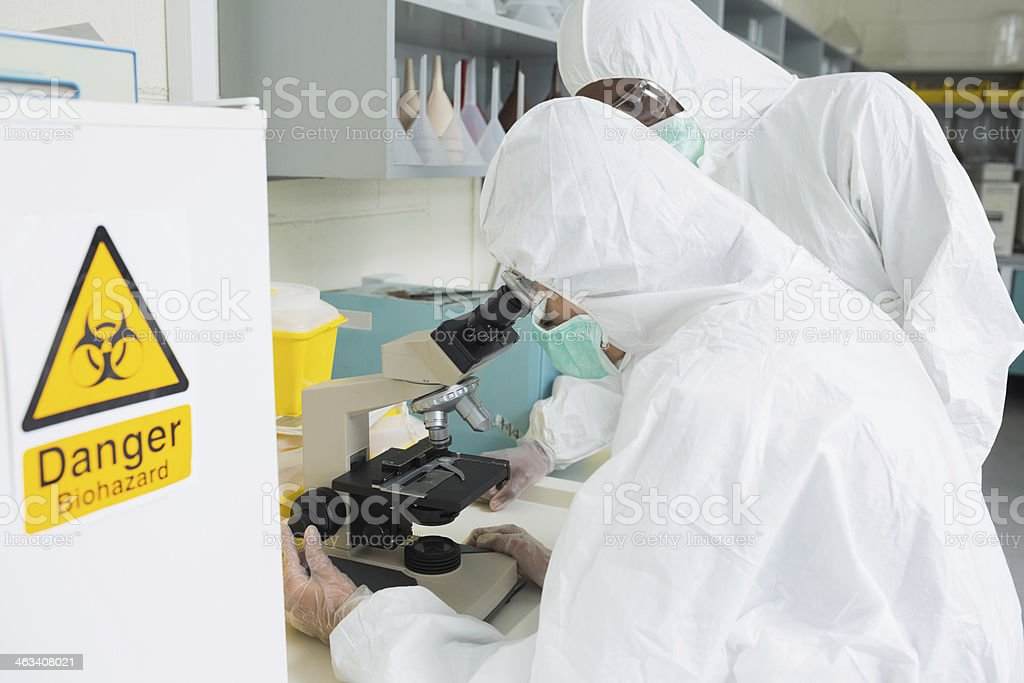 People wearing protective suits looking at microscope stock photo