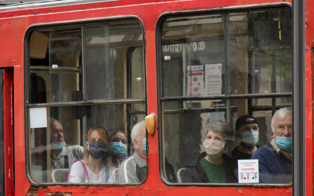 People wearing surgical face masks while  sitting and riding in a window seat of a tram