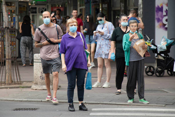 People wearing surgical masks standing at crossroad and waiting to cross the street