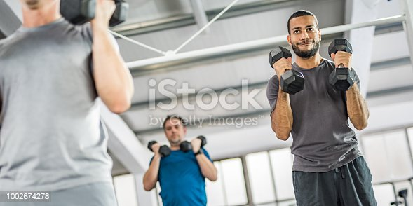 1069872470istockphoto People weight training in gym 1002674278