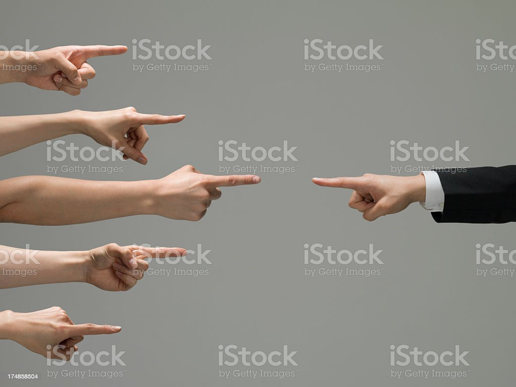 People who point at a businessman stock photo