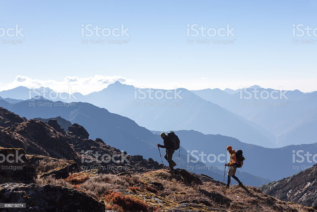 People with Backpacks and trekking Sticks traveling in Mountains – Foto