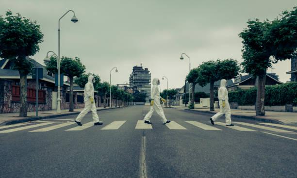 Menschen mit bakteriologischen Schutzanzügen im Crosswalk – Foto