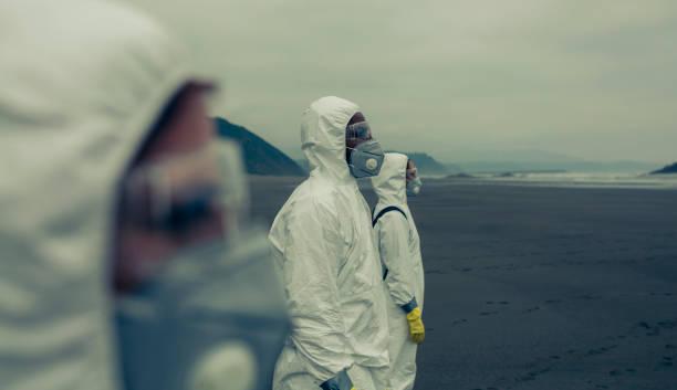 Menschen mit bakteriologischen Schutzanzügen mit Blick aufs Meer – Foto